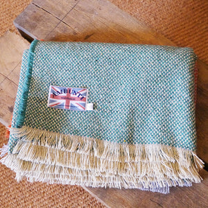 Crosshatch jade green throw on a wooden table.