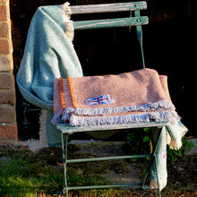 Jade green and rustic orange crosshatch recycled wool throws draped over the back of an outdoor chair.