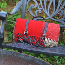 Red and grey waterproof wool picnic blanket with leather carry straps on a chair outside.