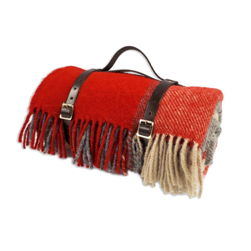 Red and grey waterproof wool picnic blanket with leather carry straps.