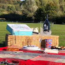 Red slate greu check picnic blanket spread out in a field