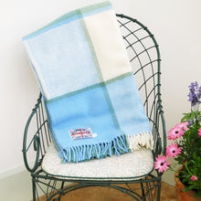 Sea cream blue pure wool check throw folded up over the back of a chair in the conservatory.