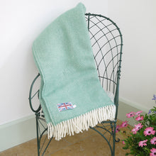 Sea green wool fishbone throw draped over the back of a chair.