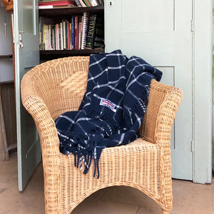 navy blue wool throw draped over a wicker conservatory chair