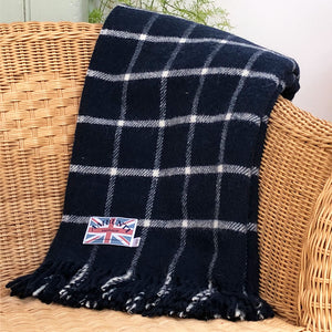 dark blue welsh wool throw folded over the back of a chair in a sun room