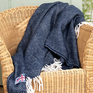 navy blue herringbone throw draped over a wicker chair
