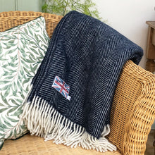 dark blue herringbone throw folded over a conservatory chair