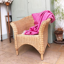cerise beehive wool throw draped over the back of a whicker chair