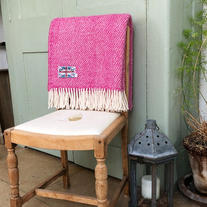 pink beehive wool throw draped over the back of a four legged chair