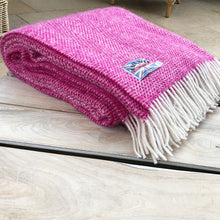 pink beehive wool throw folded up on a coffee table