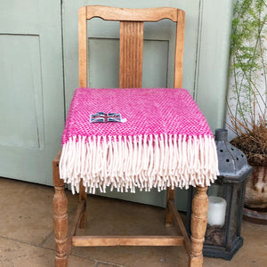 pink wool throw folded up on the seat of a wooden chair