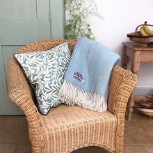light blue herringbone wool throw folded up and draped over the arm of a conservatory chair