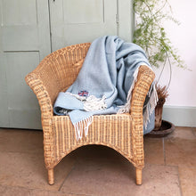 duck egg herringbone throw draped over a wicker chair