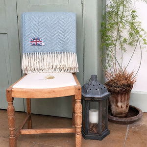 light blue herringbone wool throw folded over the back of a kitchen chair