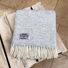 grey welsh wool throw folded up on a coffee table