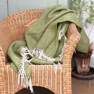 green beehove wool throw draped over a wicker conservatory chair