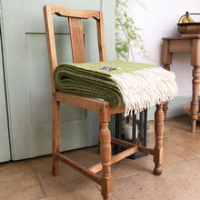 welsh green blanket folded up on the seat of a wooden conservatory chair