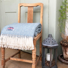 petrol blue welsh wool throw folded up on the seat of a wooden chair
