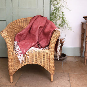 terracotta throw draped over a wicker chair