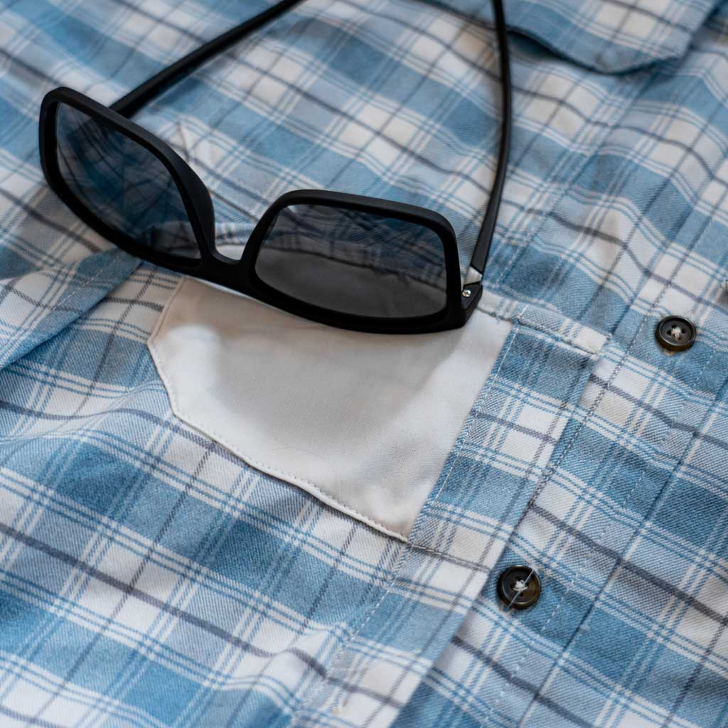 Photo showing eyeglass cleaner built into shirt, with sunglasses