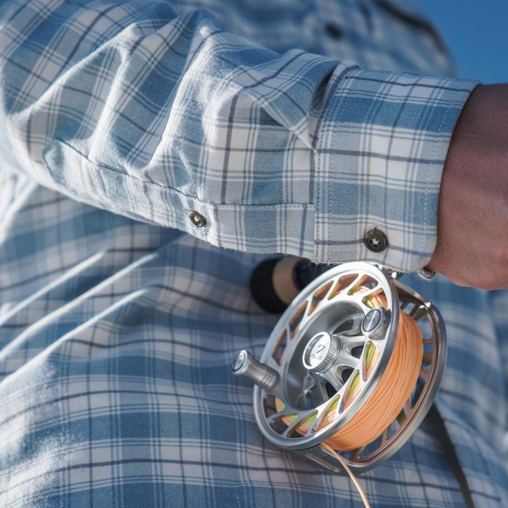 Close up of fishing reel, and sleeve of Blue Bison shirt