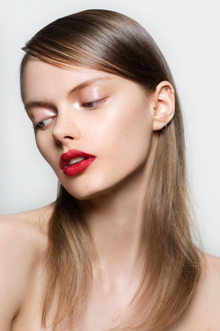 Girl looking down with glossy eyelids and red lip