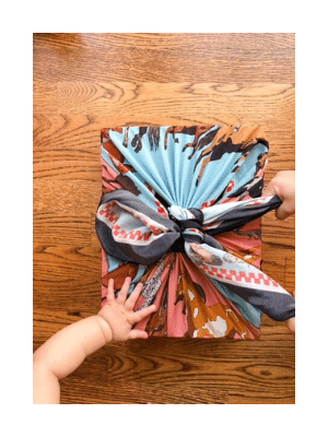 gift wrapped in fabric, baby hand and toddler's hand on wooden floor