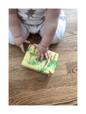 gift wrapped in kid's drawing, baby hands on wooden floor.