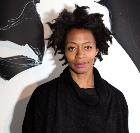 Kara walker in front of one of her black and white pieces
