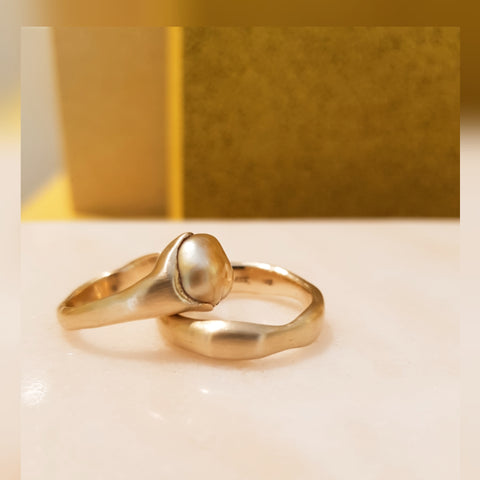 Wedding rings in 14karat gold with a sustainable golden south sea keshi pearl.