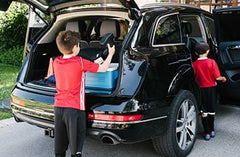 Boy loading his Clek Ozzi Booster Seat into the trunk | ANB Baby