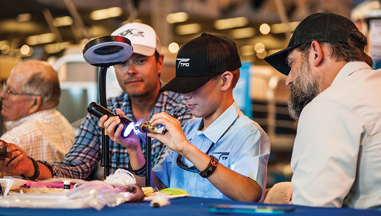 Braden tying a craft fur minnow at Lefty Kreh's Celebration of Life in 2018 while Temple Fork Outfitters Advisory Staff Member, Blane Chocklett, and fellow TFO Ambassador, Chris Thompson watch.