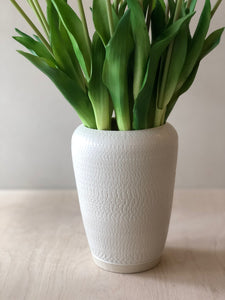 Tall white vase with chattering decoration