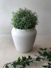 Small white vase with chattering decoration