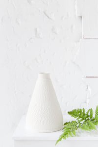 Tall white pyramid vase with chattering decoration