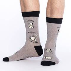 Men's feet in gray and black socks with funny pictures of yoga dog