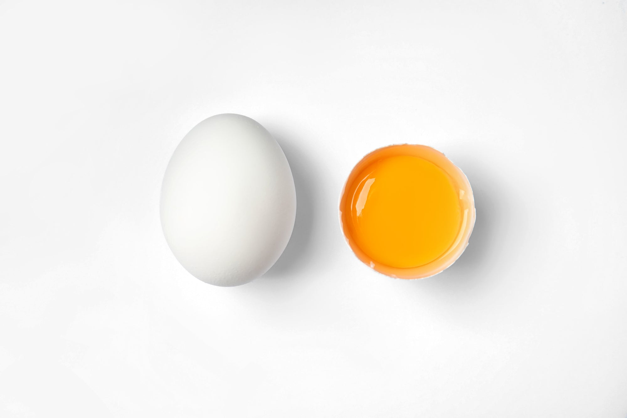 Two eggs on a white background one whole the other broke in half with the yolk in the half shell