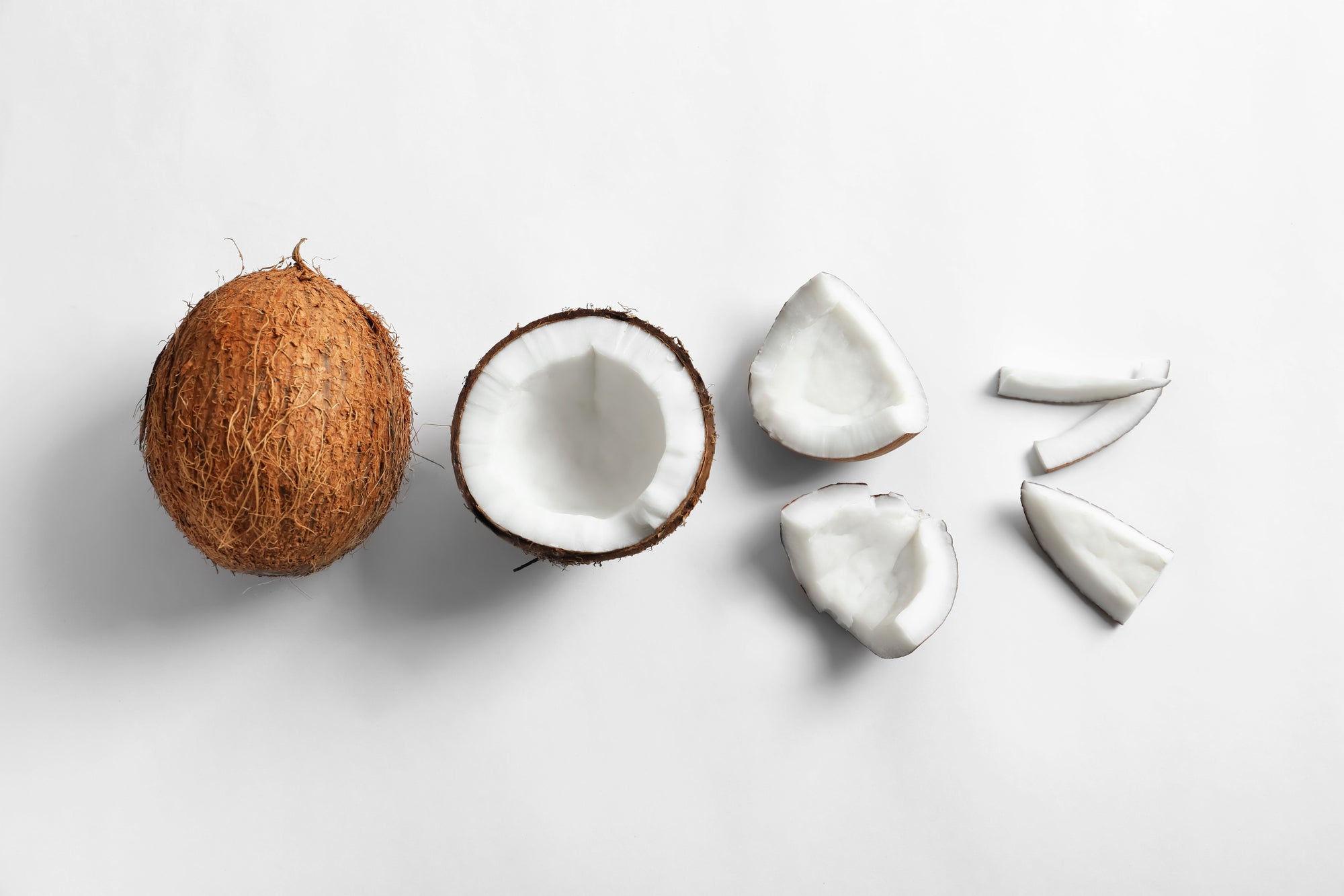 Coconuts on white background with a full coconut and one that has been cracked into pieces
