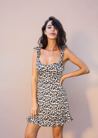 Leopard mini dress with tie straps, sweetheart neck line with small ruffle trim on the neckline and hem