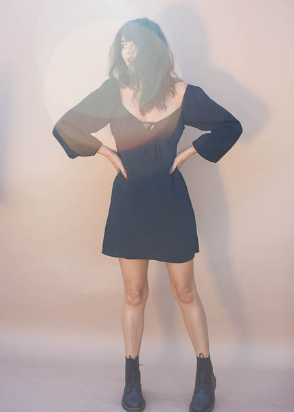Long sleeve, little black dress with peasant top. Mini dress with hidden zipper and tie front detail .