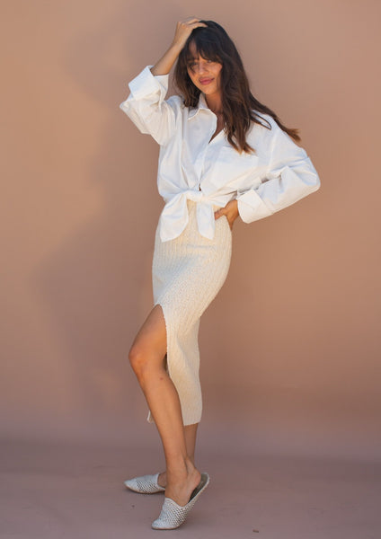 Ivory knit midi skirt with leg slit. Stretchy with a ribbed texture.