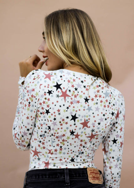 colorful star printed bodysuit with long sleeves and button front detail