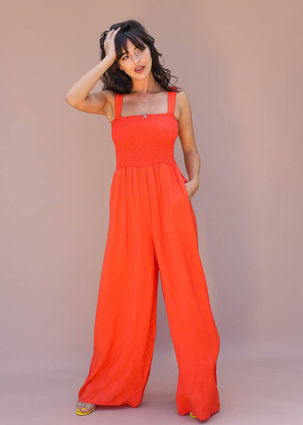 coral orange wide legged jumpsuit with elastic top and has pockets
