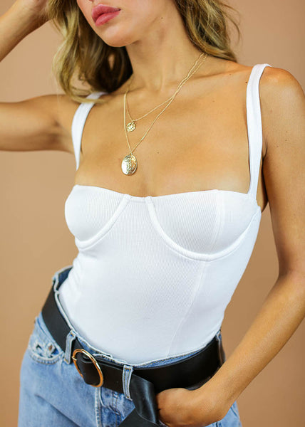 ribbed bodysuit with bra cups detail and button bottom enclosures. comes in black and white