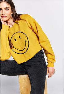 cropped sweather with raw edges. Smiley face logo on front. Comes in gold.