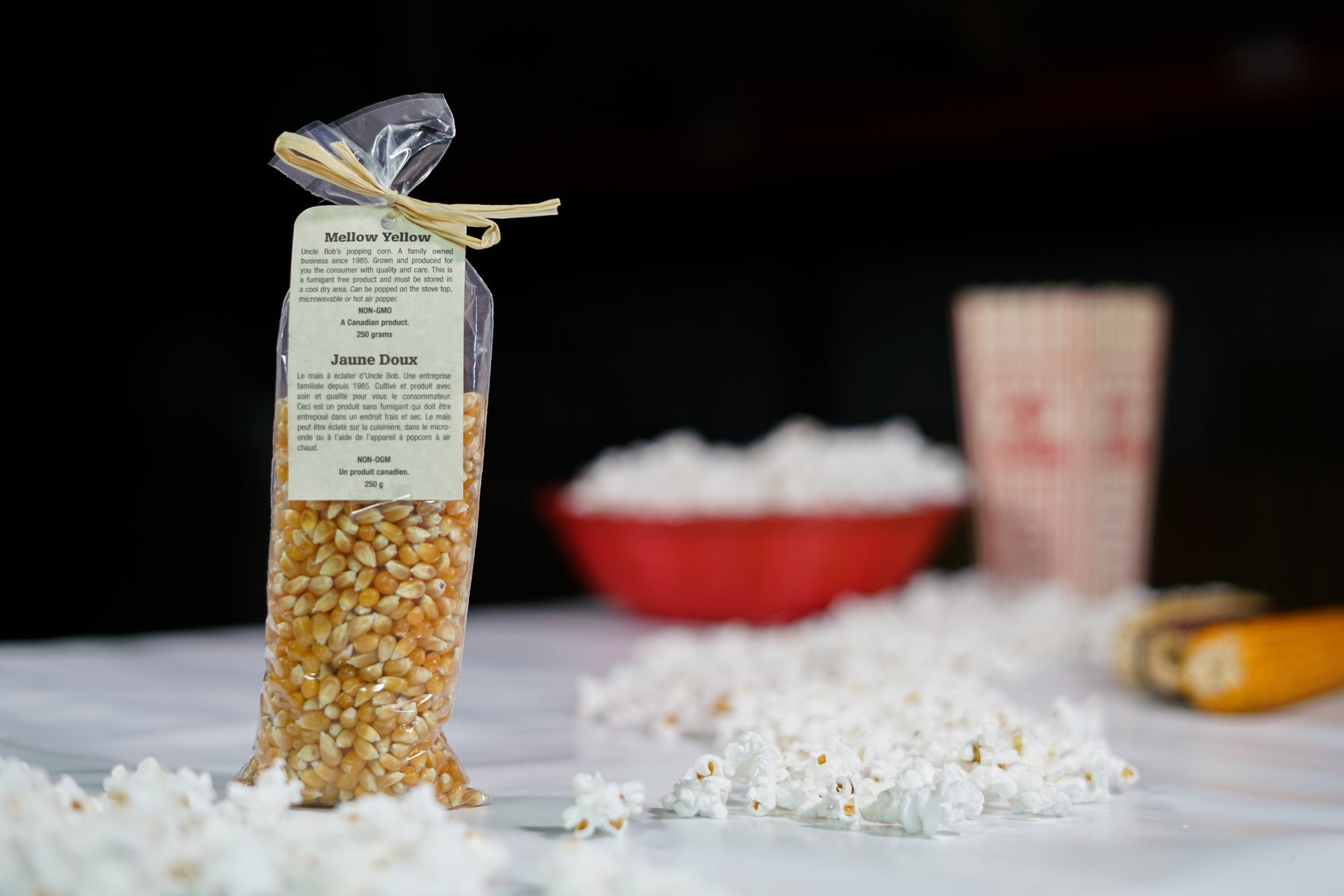 Yellow coloured popcorn kernels in a 250 gram bag with decorative tag.