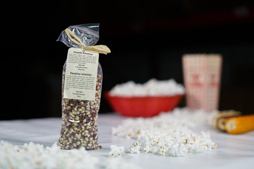 Purple coloured popcorn kernels in a 250 gram bag with decorative tag.