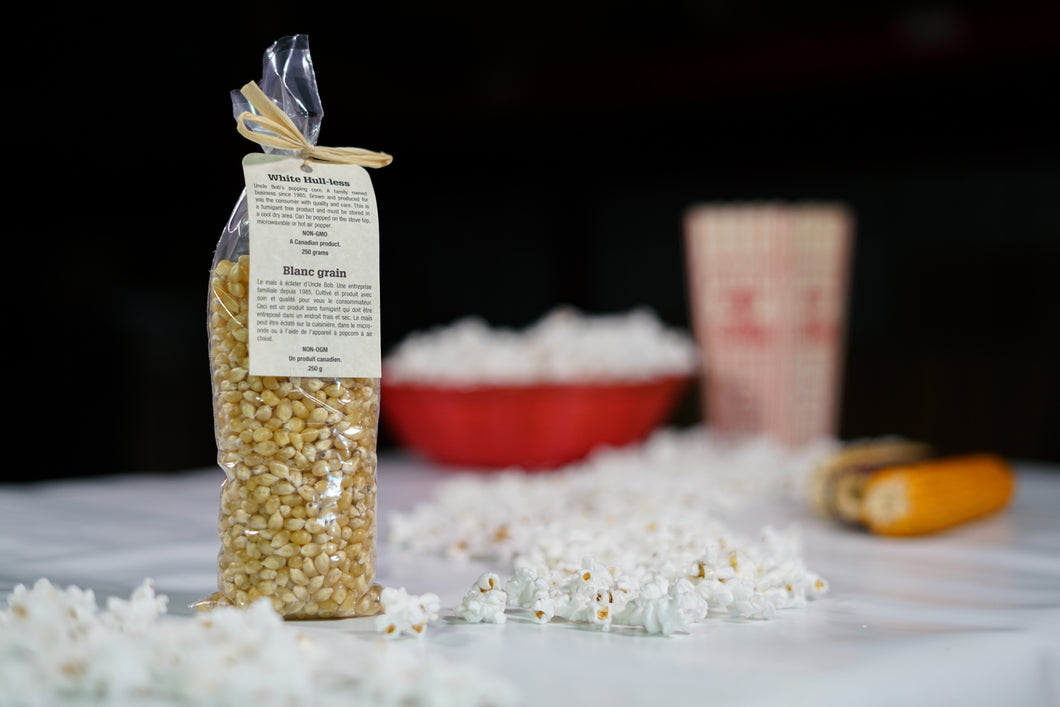 White coloured popcorn kernels in a 250 gram bag with decorative tag.