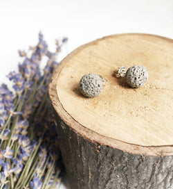 two light grey spherical stud earrings laying on wood disk with dried lavender in the backgroun