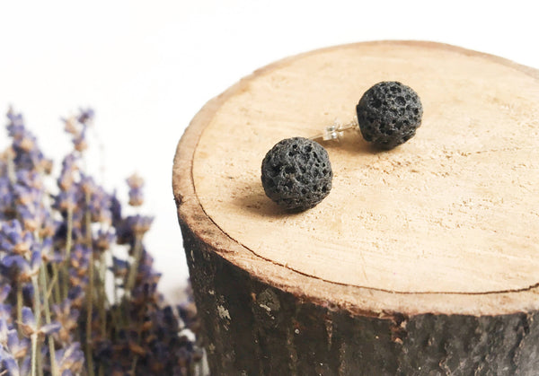 two black spherical stud earrings laying on wood disk with dried lavender in the background